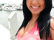 Hot brunette cutie walks around the waterfront