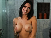 Sexy brunette with a tattoo on her arm goes for shower